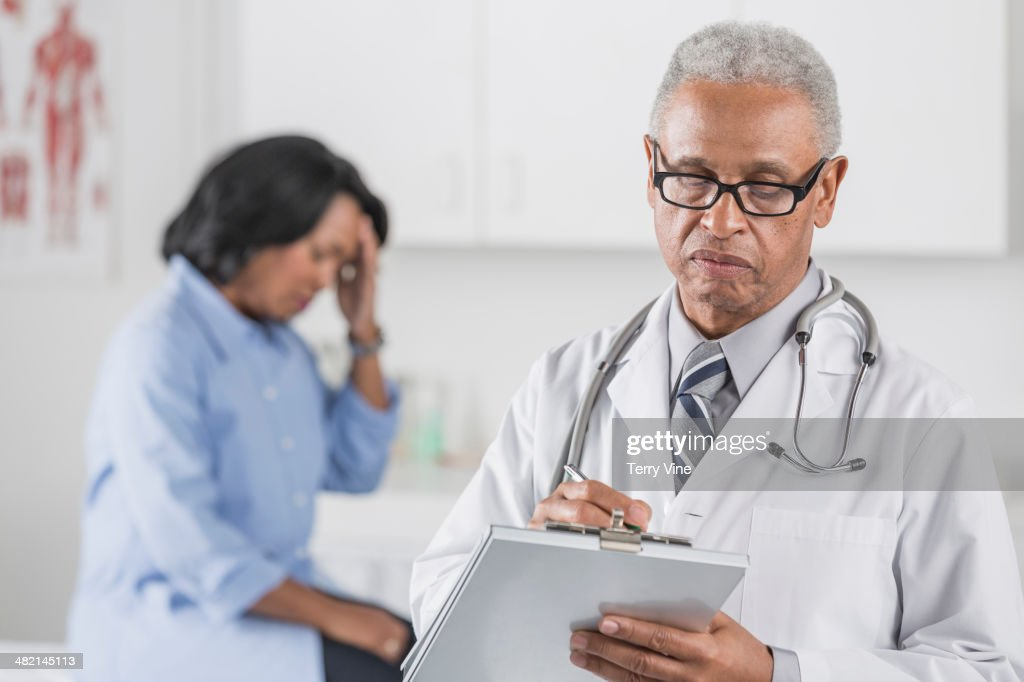 African American doctor writing on clipboard with patient in background : Stock Photo