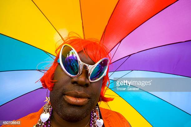 African american drag queen with Rainbow umbrella at the Gay Pride festival . This was at the street party that takes place around City Hall after...