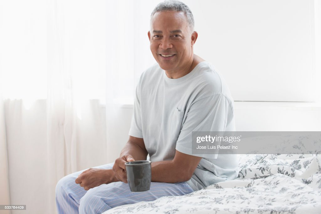 African American drinking cup of coffee on bed : Foto stock