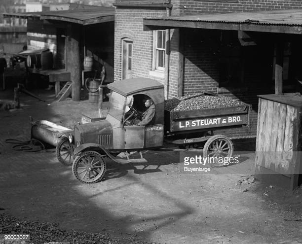African American Driver has a load of coal ready for delivery the company truck