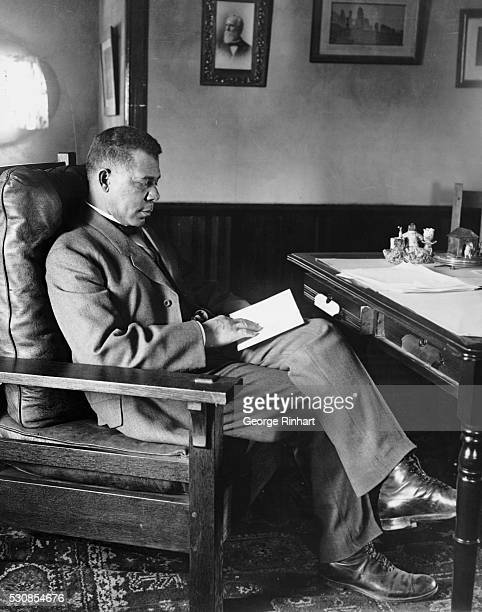 African American educator Booker T Washington is shown seated and reading behind a desk