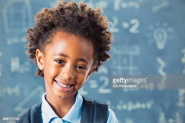 African American elementary schoolgirl in front of blackboard