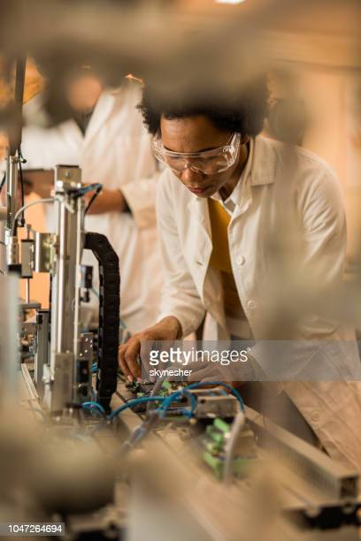 African American engineer testing machine part quality in a laboratory.