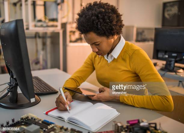 African American engineer using digital tablet and taking notes in laboratory.