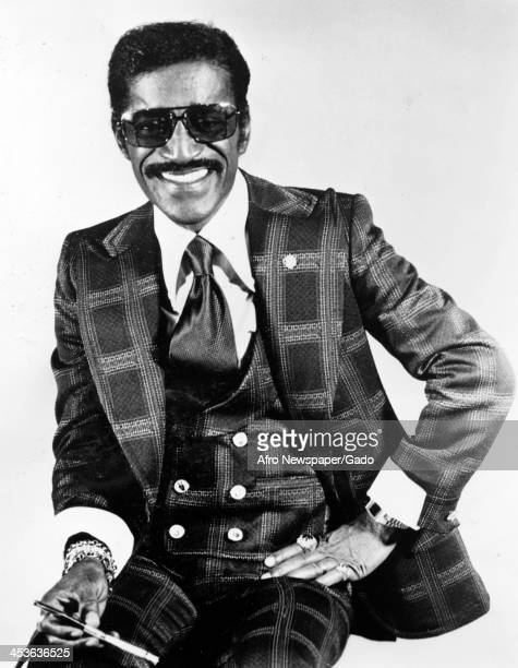 African American entertainer Sammy Davis Junior poses for a portrait in a suit and sunglasses holding a cigarette April 30 1977