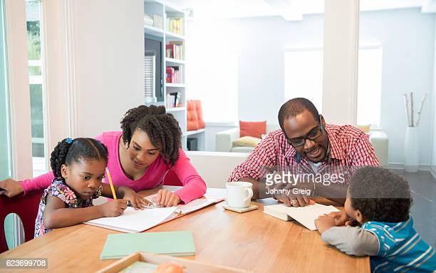 African American family at home, children doing homework