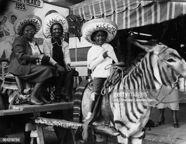 African American family in Mexico two women sitting on a wagon young child riding a donkey which is painted to look like a zebra all wearing...