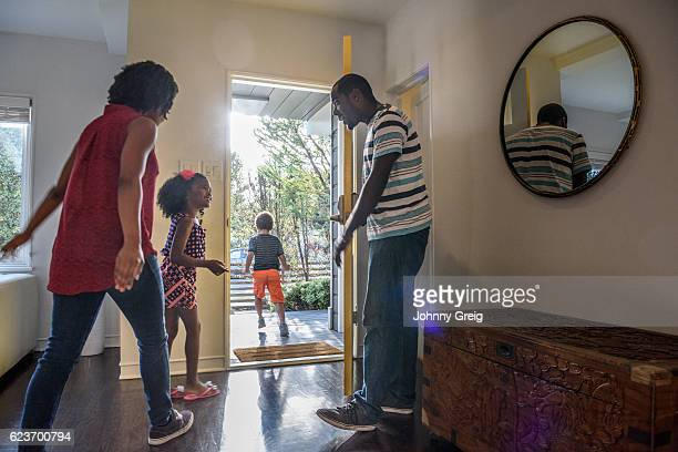 african american family leaving the house, father holding door - leaving stock pictures, royalty-free photos & images