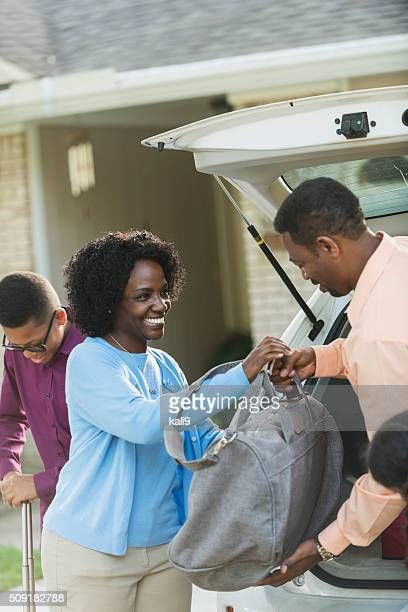 African American family loading luggage into car