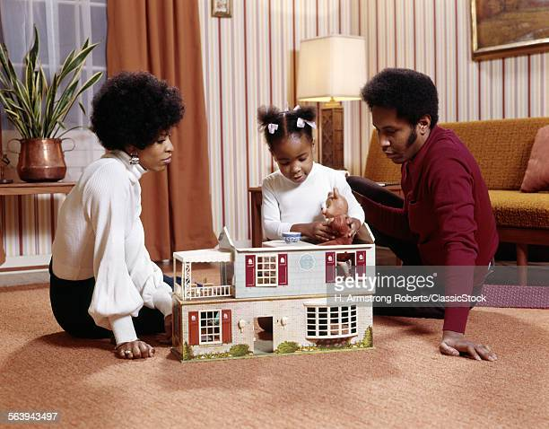 1970s AFRICAN AMERICAN FAMILY MOTHER FATHER GIRL DAUGHTER PLAYING ON FLOOR WITH DOLLHOUSE