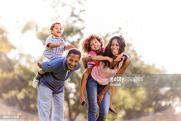African American family piggybacking in nature and having fun.