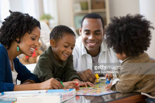 african american family playing board game together - leisure games stock pictures, royalty-free photos & images