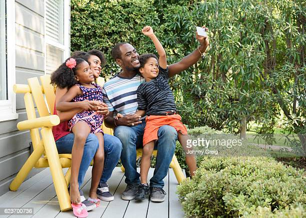 african american family posing for self portrait photo in garden - mom sits on sons lap stock pictures, royalty-free photos & images