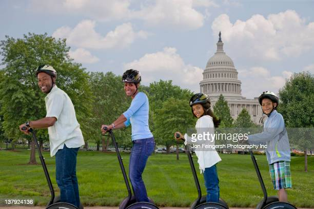 African American family sightseeing on motor scooters