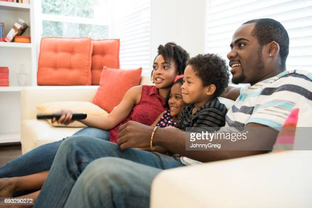African American family sitting on sofa watching tv