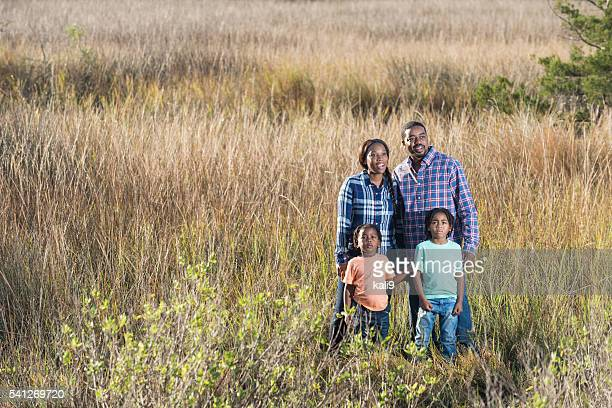 African American family standing together in a field