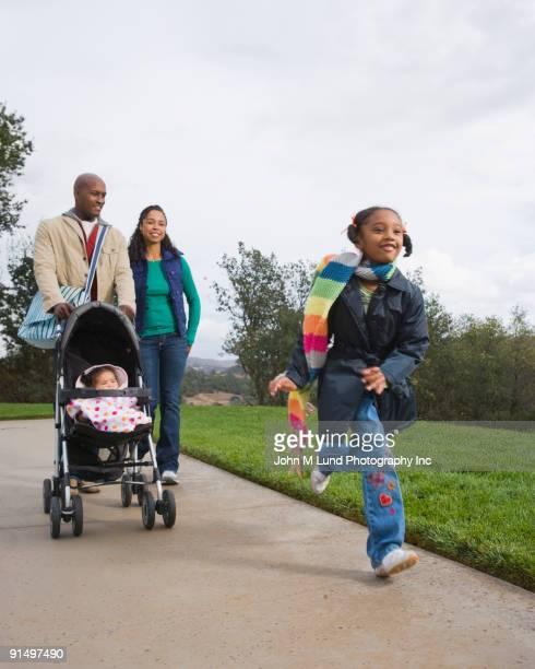 african american family taking walk with stroller - mom flirting 個照片及圖片檔