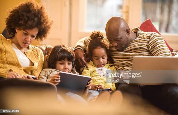 Afrikanische amerikanische Familie mit kabelloser Technik wie zu Hause fühlen.