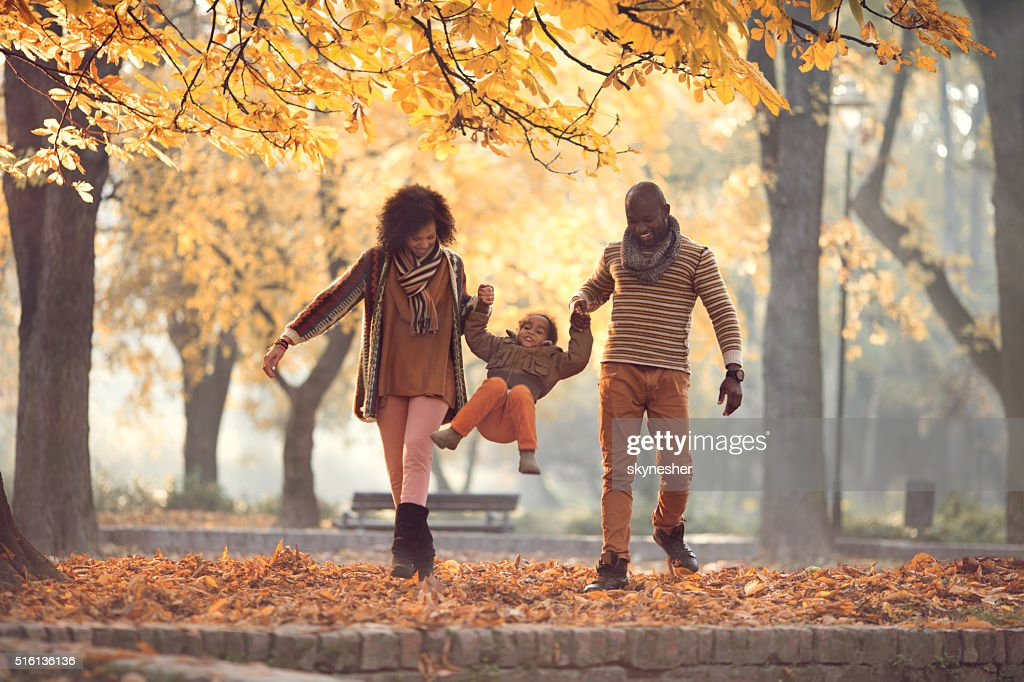 African American family walking and having fun in autumn park. : Stock Photo