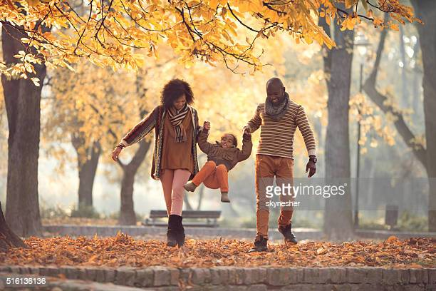 African American family walking and having fun in autumn park.