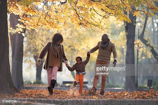 African American family walking in autumn park and having fun.