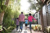 African American family walking in garden, rear view
