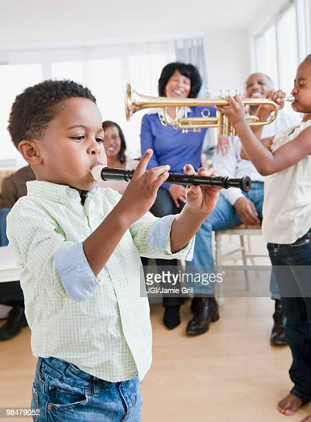 african american family watching children play instruments - recorder musical instrument stock photos and pictures