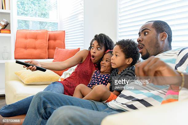 African American family watching television together