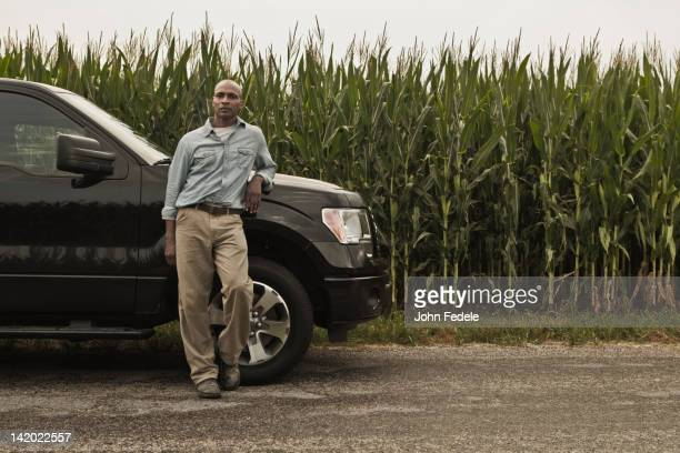 African American farmer leaning on car next to crop