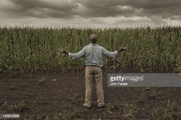 African American farmer standing in field with arms outstretched