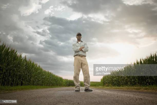 african american farmer standing on road through crops - vista de ángulo bajo fotografías e imágenes de stock