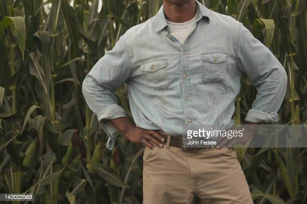 african american farmer standing with hands on hips - mid section stock photos and pictures