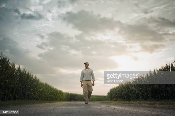 African American farmer walking on road through crops