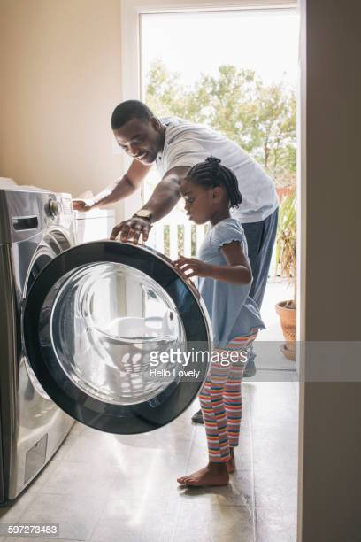 african american father and daughter doing laundry - laundry stock pictures, royalty-free photos & images