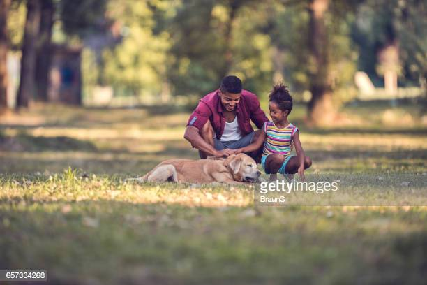 african american father and daughter with their dog in nature. - one animal stock pictures, royalty-free photos & images