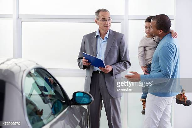 African American father and son discussing with a car salesperson.