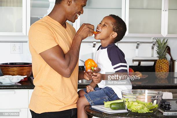 African American father and son eating vegetables in kitchen