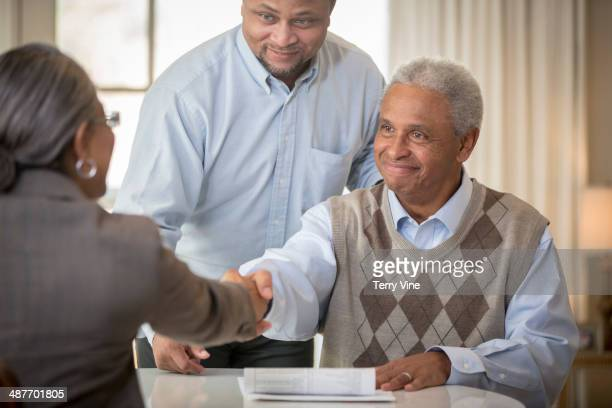 African American father and son shaking hands with businesswoman