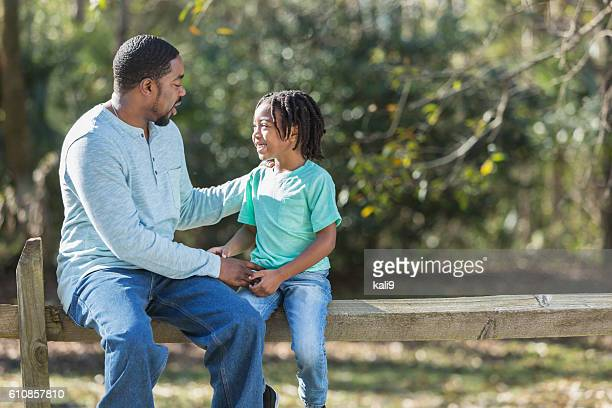 African American father and son sitting outdoors talking
