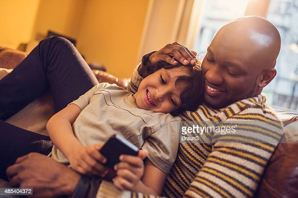 African American father and son text messaging on cell phone.