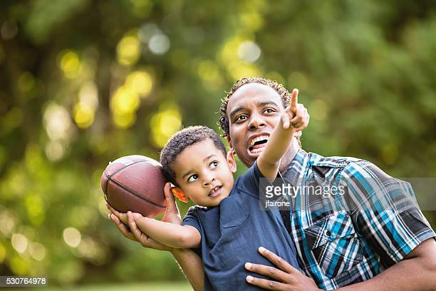 African American Father and Young Son outdoors playing football