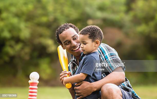 african american father and young son outdoors playing t ball - baseball sport stock pictures, royalty-free photos & images