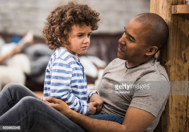African American father consoling his small sad son at home.