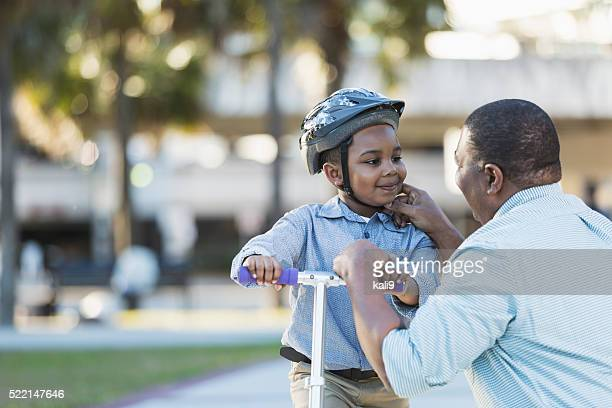 African American father helping boy on scooter