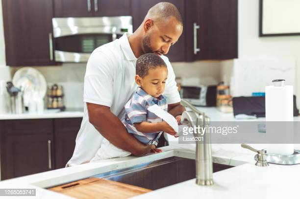 african american father helps his son wash his hands - kitchen paper stock pictures, royalty-free photos & images