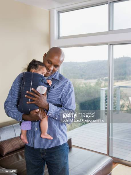 african american father holding baby - black man holding baby stock photos and pictures