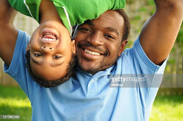 african american father playing happily with his son - mixed wrestling stock pictures, royalty-free photos & images