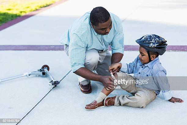 African American father putting bandage on son's knee