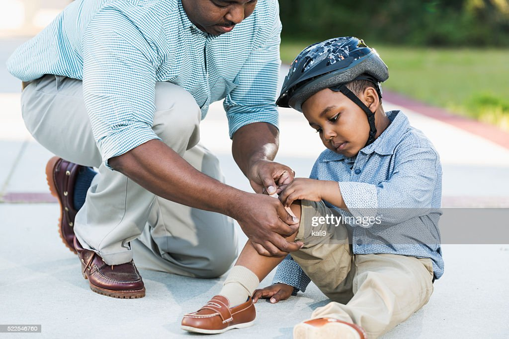 African American father putting bandage on son's knee : Stock Photo
