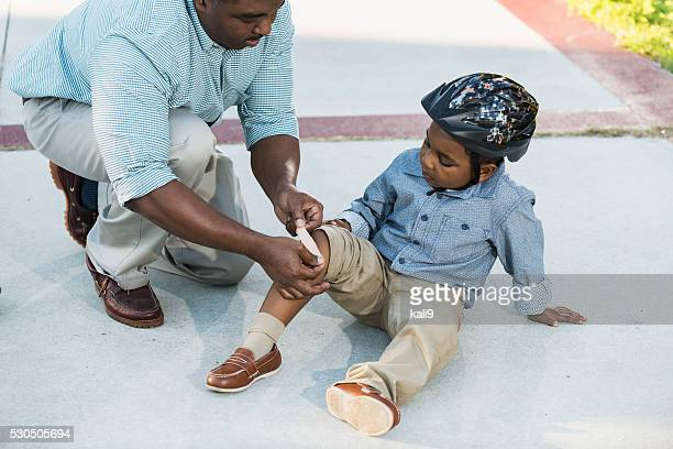 african american father putting bandage on son's knee - leg wound stock pictures, royalty-free photos & images